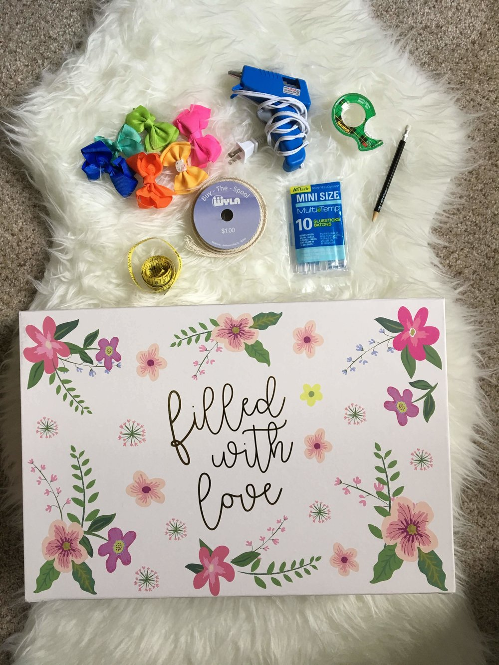 You will need a  keepsake/storage box, spool of ribbon, glue gun, glue sticks, transparent tape, pencil, measuring tape, and scissors  (not shown), and  bows  of course!